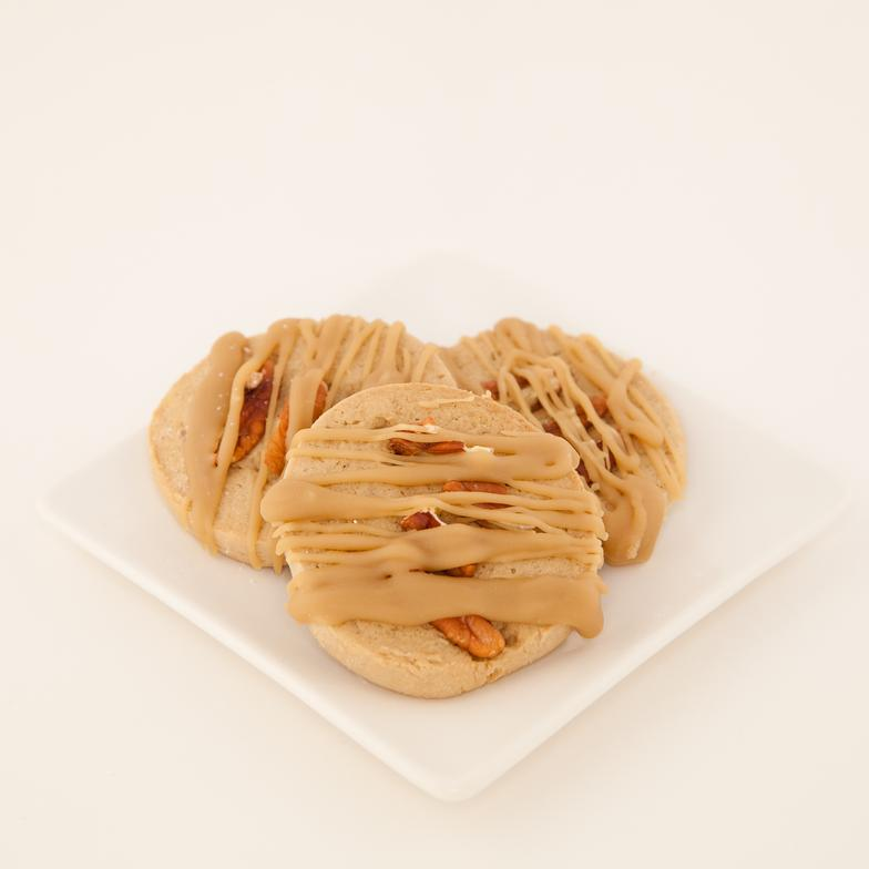 Maple cookie topped with pecans and drizzled with a brown sugar glaze. A favorite guy cookie!