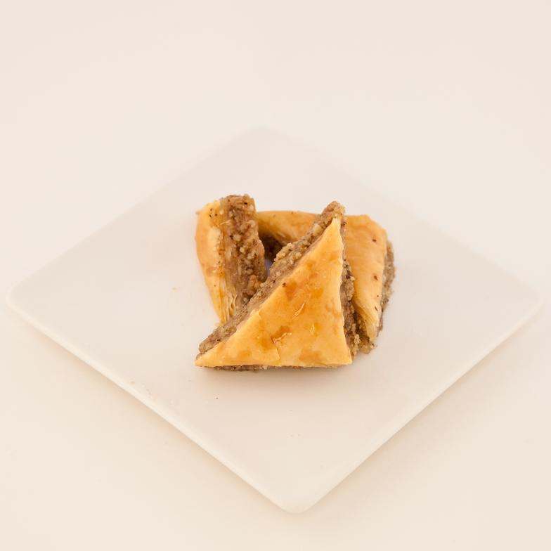 A sweet flaky Greek pastry with a layer of sweetened walnuts and a hint of almond flavoring, in lined paper cups ready to serve.